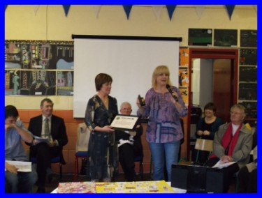 Here Mrs. Commons is presented with a from Children Helping Children charity.