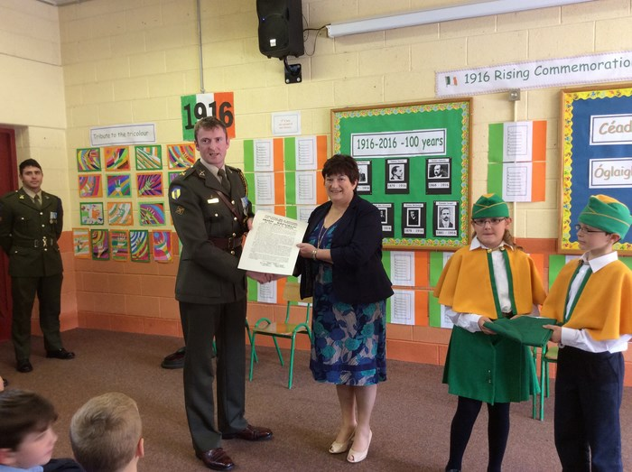 Commandant Joe Freeley presents Mrs Cunnane with a copy of the 1916 Proclamation