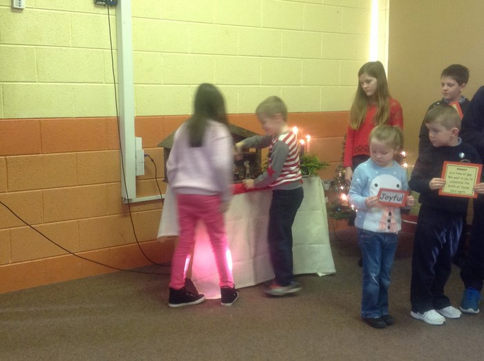 2nd Class pupils place figure of the Infant Jesus in the crib