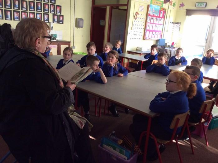 Retired teacher Mrs Higgins reads to 2nd Class